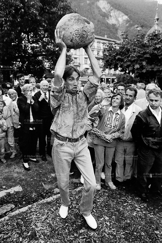Switzerland. Canton Bern. Interlaken. A day before the swiss national Unspunnen stone throwing championship, an amateur contest takes place during the Unspunnen Festiva. A young man lifts above his head a stone (weight  20 kg) and throws it as far away as he can. © 1993 Didier Ruef