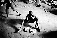 Rwanda. Gitagata. Prison for 152 children, aged 4 to 14, all convicted for active involvement (murder) in the 1994 rwandese genocide. Reeducation camp for minors. A boy seated on the ground eats his food. © 1995 Didier Ruef