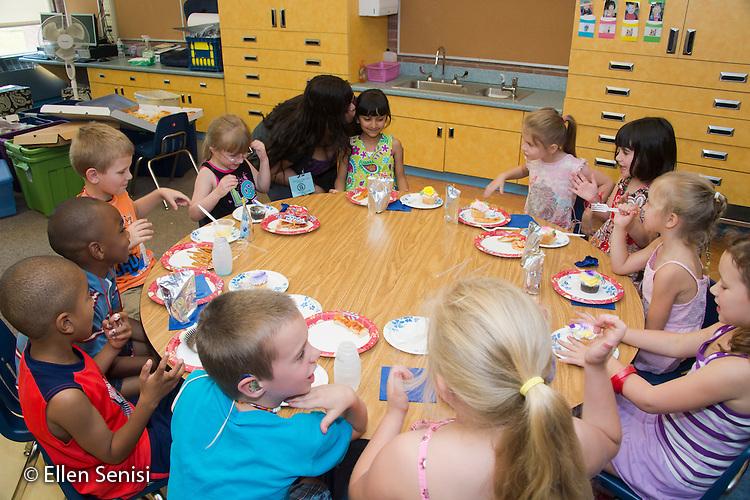 MR / Schenectady, NY. Zoller Elementary School (urban public school). Kindergarten classroom. Mother (Caribbean American) kisses her daughter at classroom birthday party. MR: AM-gKw. ID: AM-gKw. © Ellen B. Senisi.