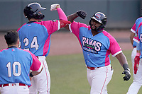 """Tyreque Reed (38) of the Greenville Drive, right, celebrates his home run with Tyler Dearden (24) in a game against the Brooklyn Cyclones on Saturday, May 15, 2021, at Fluor Field at the West End in Greenville, South Carolina. Drive players were wearing jerseys for the """"Ranas de Rio de Greenville"""" (Greenville River Frogs), as part of Minor League Baseball's """"Copa de la Diversion"""" program. (Tom Priddy/Four Seam Images)"""