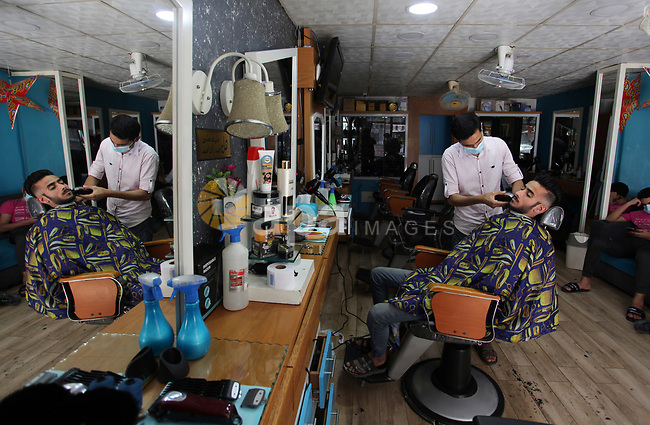 Palestinian barber, wears a mask and gloves, shaves for clients, marking International Workers' Day, in Gaza city, on May 01. 2021. Youth (19- 29 years) are the most group suffering from unemployment. Thus, the unemployment rate among youth reached about 39%; 24% in the West Bank and 67% in Gaza Strip. Moreover, the youth graduates of those who hold a scientific qualification of an intermediate diploma or higher are the most group suffering from unemployment, as this rate reached about 54%; (36% in the West Bank and 79% in Gaza Strip). Photo by Mahmoud Ajjour