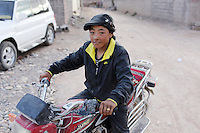 A Tibetan boy on a motorbike in Zaduo, in the far interior of the Tibetan Plateau, in western China. Relocation communities been created to house nomadic herders moved from the highland grasslands. The nomads have been blamed for contributing to the deterioration of the grasslands, so have been moved, sometimes forcibly, into newly built towns that can be found across the plateau.