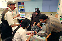 """Cris L'ariste an Israeli  medical clown who works in Hadassah and he is a member of a group call """"Dream Doctor"""", distracts a Palestinian boy as a nurse introduces a line on the vein with the help of the parents to take a blood test in the Oncology Day Care unit at Hadassah Ein Karem hospital. Photo by Quique Kierszenbaum."""