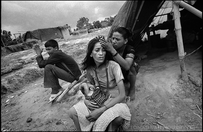 Laxmi Shahi, 31, who fled a Maoist controlled area of Nepal nurses a child while another refugee picks lice out of her hair in the Kirin Khola Camp for internally displaced persons (conflict refugees) in Nepal on Saturday, 25 June 2005.<br />