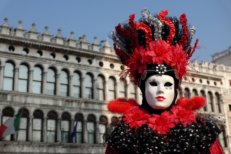 Woman dressed in traditional mask and costume for Venice Carnival standing in Piazza San Marco, Venice, Veneto, Italy