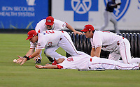 Members of the Rome Braves and Greenville Drive stage a mock battle, with Matt Marquis (23) pretending to fall on a baseball-grenade, during a lengthy rain delay before a game on July 5, 2012, at Fluor Field at the West End in Greenville, South Carolina. (Tom Priddy/Four Seam Images)