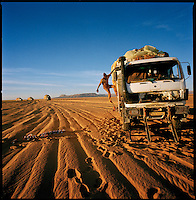 Sahara desert, Libya-Chad, November/December 2004..Every week, a convoy of 40 privately owned Libyan trucks loaded by the WFP with about 1000 metric tons of western food aid cross 2500 km of deep desert across Libya and Chad to reach more than 200 000 refugees from Darfur in camps near the Sudanese border. The mechanic of this truck has just made a complete oil change...and leaves oil cans and a patch of dirty motor oil behind...