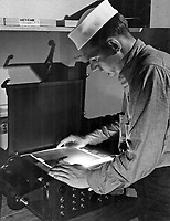 Students of Class III Aerial Photography preparing negatives for printing.    J. N. McDonald adjusts the printing light on the military mapping printer to suit his negative.