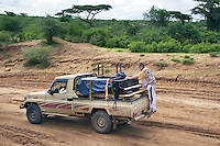 """Ethiopia. Southern Nations, Nationalities, and Peoples' Region. Omo Valley. On the road to Korcho Village and the Kara tribe. Robert Wolken stands on the bumper of a Toyota pick-up truck. He is a professional piano tuner and takes care of Marc Vella's Yamaha Grand Piano. Marc Vella is a french musician and a nomadic pianist. Over the last 25 years he has travelled with his piano in around forty countries to celebrate humanity. Creator of """"La Caravane amoureuse"""" (The Caravan of Love) he takes people with him to say """"I love you"""" to others and """"lovingly conquered"""" their hearts and souls. The Omo Valley, situated in Africa's Great Rift Valley, is home to an estimated 200,000 indigenous peoples who have lived there for millennia. Amongst them are 1,000 to 2,000 Karo who dwell on the eastern banks of the Omo river. Southern Nations, Nationalities, and Peoples' Region (often abbreviated as SNNPR) is one of the nine ethnic divisions of Ethiopia. 8.11.15 © 2015 Didier Ruef"""
