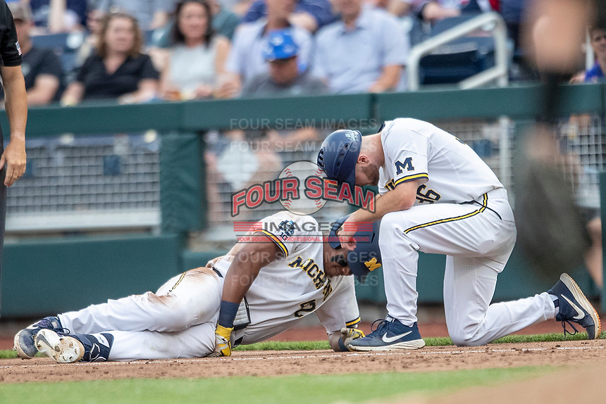 Michigan Wolverines designated hitter Jordan Nwogu (42) talks with first base coach Michael Brdar (36) on the ground after being injured in the third inning against the Vanderbilt Commodores during Game 2 of the NCAA College World Series Finals on June 25, 2019 at TD Ameritrade Park in Omaha, Nebraska. Vanderbilt defeated Michigan 4-1. (Andrew Woolley/Four Seam Images)