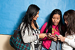 Education high school three female students in corridor between classes looking at cell telephones or devices.