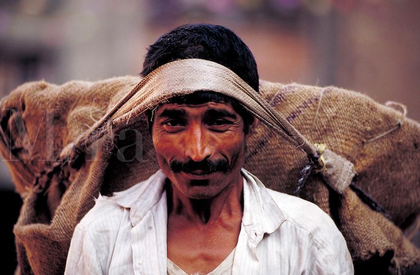 Portrait of a smiling man carrying large burlap bag by tumpline; full face; head and shoulders. Kathmandu, Nepal.