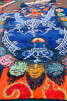 Rock painting of blue protector deity of the Gelugpa Buddhist order, Yama Dharmaraja, adorned with skulls and severed heads, on the sacred circuit, or kora, around the monastery walls of Sera Monastery, Lhasa, Tibet, China.