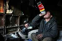 MONGOLIA. Ulaan Baatar. Otguntugs,28, (right) and Ounsuren (left), 36, use what money they have from collecting bottles to purchase cheap Russian Vodka which they drink in order to stave off the bitter cold that embraces Ulaan Baatar for large portions of the year.<br /> As the global financial crisis grips Asia, Mongolia is feeling the implications first hand as the country suffers from rising inflation pushing the price of food and fuel ever upwards. For the country's homeless, who live in sewers and abandoned garages in the capital and already face extreme discrimination and are denied access to basic health and social care, their lives are hanging in the balance. 2008