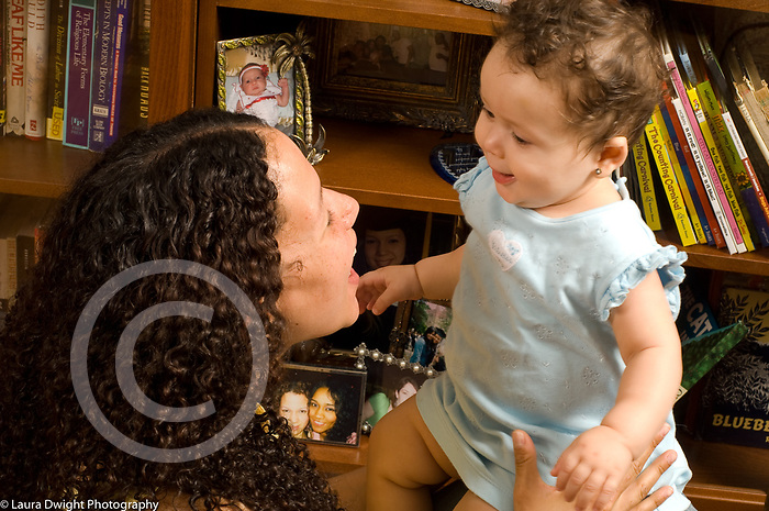 9 month old baby girl interacting with mother face to face, smiling happy