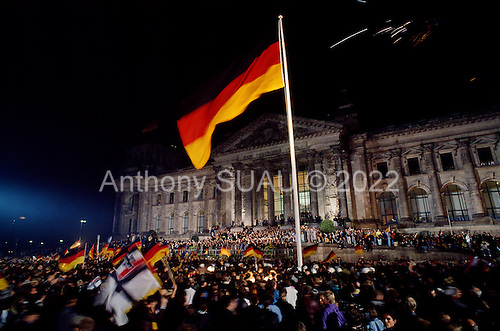 Berlin, Germany<br /> October 3, 1990<br /> <br /> In front of the Reichstag, the two Germany's -East and West - were reunited the second this massive German flag reached the top of the flag pole.<br /> <br /> Large crowds gathered for the event, nearly one year after the Berlin Wall was opened allowing East Germans to travel freely to the West. By October 1990 almost nothing remained of the wall.