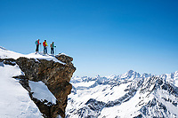 A group of ski tourers on the summit of the Steinhüshoren looking out at the Bernese Oberland while on a ski tour of the Berner Haute Route, Switzerland
