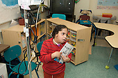 MR / Albany, NY.Langan School at Center for Disability Services .Ungraded private school which serves individuals with multiple disabilities.Student in classroom holds a book he wants to read while having gastric tube feeding. Boy: 7, African-American, Pierre Robin syndrome, limited verbal output with expressive and receptive language delays, has Passy Muir valve to redirect air flow to produce speech .MR: Smi24.© Ellen B. Senisi