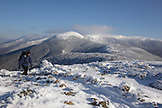 A hiker on the summit of Mount Pierce in the White Mountains, New Hampshire USA. The Presidential Range can be seen in the background