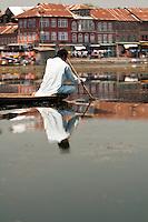Kashmiri man and reflection paddling traditional shikara on Dal Lake, Srinagar, Kashmir, India.