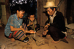 Northern Thailand. Thai family addicted to opium, their child smoking opium. Peasant farmers in home. The boy is 8 years old. Chiang Rai province. 1990s