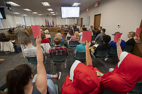"""Members of the audience express their opposition with red cards Thursday July 15, 2021 at the Washington County Quorum Court meeting. A resolution before the court declared Washington County a """"pro-life"""" county.  Patrick Deakins, justice of the peace for District 5 in northeast Washington County, sponsored the resolution. Under Arkansas law, a resolution adopted by the Quorum Court isn't a law, only a statement of policy, and doesn't have any effect under the law."""