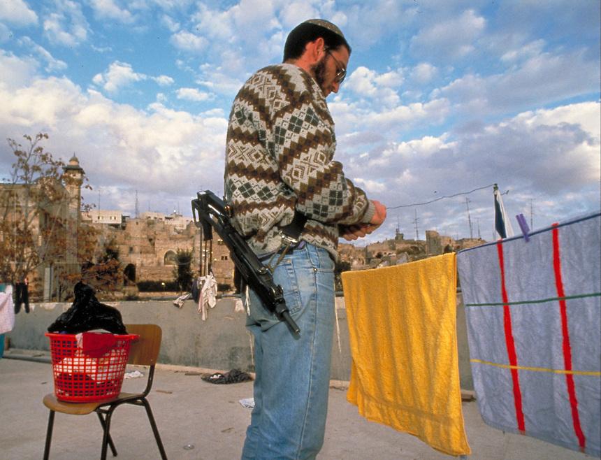 TITLE - DISTANT RELATIONS, ARMED JEWISH SETTLER HANGS LAUNDRY ATOP JEWISH YESHIVA (SCHOOL),. HEBRON ISRAEL.