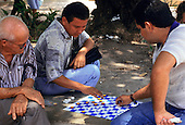Manaus, Brazil. Three men playing draughts sitting on a concrete wall. Amazonas State.