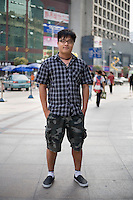 Wangyun, a student, age 24, poses for a portrait in Nanjing. Response to 'What does China mean to you?': 'China means my home and family.' (written in English)  Response to 'What is China's role in the future?': 'Hopefully, China can the leader.' (written in English)