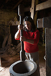 A woman grinds the shells off of raw coffee beans with a giant mortar and pestle at the  Old Mill House Coffee Experience, Santa Catarina, Brazil
