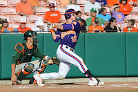 First Baseman Jon McGibbon #12 swings at a pitch during a  game against the Miami Hurricanes at Doug Kingsmore Stadium on March 31, 2012 in Clemson, South Carolina. The Tigers won the game 3-1. (Tony Farlow/Four Seam Images).