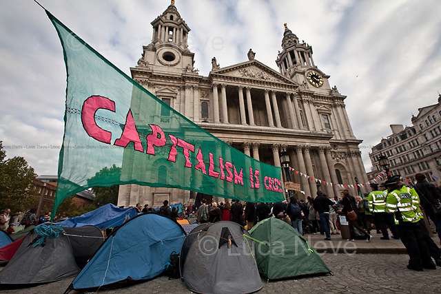 """London, 16/10/2011. Second day of the peaceful Occupation outside St Paul's Cathedral. In the early morning representatives of St Paul's asked police officers to leave the steps of the Cathedral and stop any attempt to evict the occupants. The tents are now numbered at around two hundred. The protesters have built a kitchen, and now dedicate their time to political meetings, discussions, creation of a library, placards and posters to show their messages: """"We are the 99%""""."""
