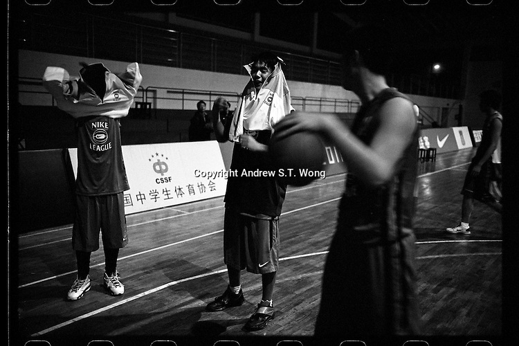 Basketball players of Huazhong Shida First Affiliated High School in Wuhan, Hubei province, try on their new uniform after a training session, December 2011.