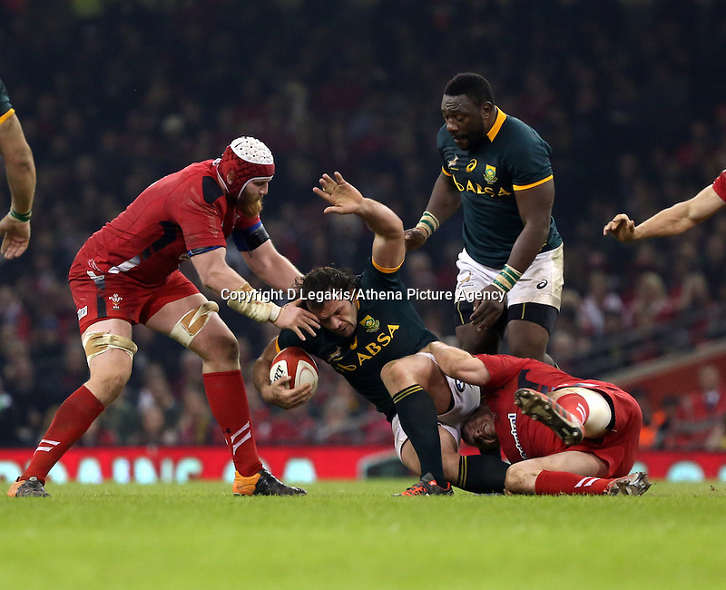 Pictured: Bismarck du Plessis of South Africa (with ball) is grabbed from behind by Gethin Jenkins of Wales, assisted by Jake Ball (L) Saturday 29 November 2014<br /> Re: Dove Men Series 2014 rugby, Wales v South Africa at the Millennium Stadium, Cardiff, south Wales, UK.