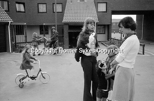 1970s modern housing development UK. Two local women with children chatting in the car free street. Kids playing on their bikes. 1977 England. Milton Keynes Buckinghamshire