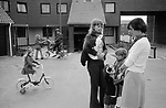 1970s modern housing development UK. Two local women with children chatting in the car free street. Kids playing on their bikes. 1977 England. Milton Keynes Buckinghamshire