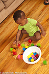 12 month old baby boy sitting playing with blocks stacking two cubes