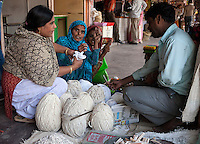 Jaipur, Rajasthan, India.  Woman Bargaining over Buying a Ball of Yarn.