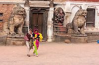 Bhaktapur, Nepal.   Women Walking Past Lions Guarding Entrance to Palace, Durbar Square.  The smaller stone sculpture to the right of the door shows Narasimha, Man-lion Avatar of Vishnu, Victorious over the Demon Hiranyakasipu.