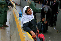 A Palestinian woman pauses as she crosses the Hawara checkpoint in Nablus, West Bank, November 05, 2006. The Hawara checkpoint on the southern entrance of Nablus controls the movement of Palestinians between Nablus and the Southern part of the West Bank. The checkpoint, run by IDF paratroopers, doesn't limit with Israel. Photo by Quique Kierszenbaum