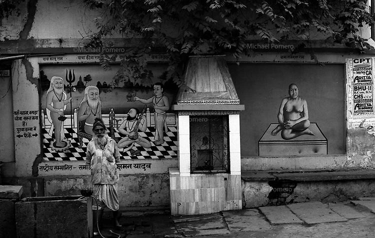 12.2010 Varanasi (Uttar Pradesh)<br /> <br /> Man using water with wall decoration behind him.<br /> <br /> Homme utilisant de l'eau avec une décoration murale derrière lui.