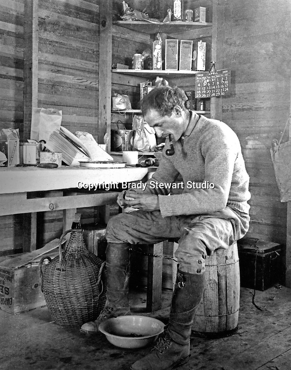 Jerome ID:  Brady Stewart peeling potatoes in his farmhouse.  A Calendar and food products in the background. Brady Stewart and three friends went to Idaho on a lark from 1909 thru early 1912. As part of the Mondell Homestead Act, they received a land grant of 160 acres north of the Snake River.  For 2 ½  years, Brady Stewart photographed the adventures of farming along with the spectacular landscapes.