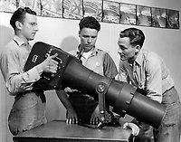 Students of Class III Aerial Photography studying the technique of  the oblique camera.  Instructor C. F. Heilig, PhoM 1/c demonstrating the long range oblique camera  (F56 with  40inchlens) to Eury, W. J. S2/c and Weise N. E. PhoM 3/c prior to using it in their class work.