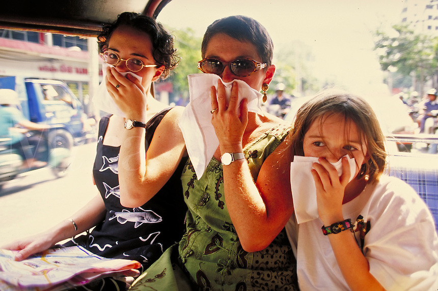 Family members cover their mouths with cloths in an attempt to breathe less of the pollution in Bangkok's air. Bangkok, Thailand.