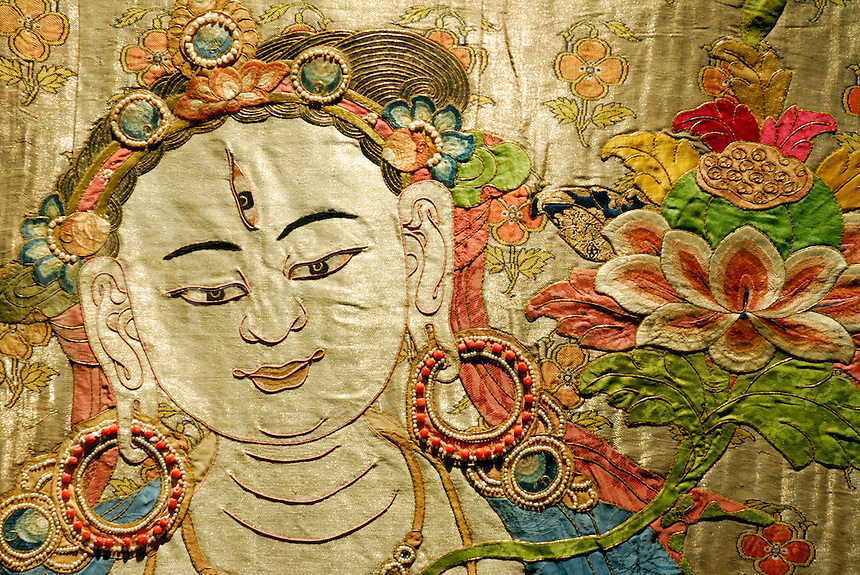 Rare 15th century thangka in embroidered silk brocade applique of female bodhisattva, Drolkar, or White Tara, with eye in forehead, protectress and wish grantor of the Tibetan people, Tibet Museum, Lhasa, China.
