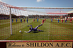 Shildon 0 Warrington Rylands 0 (4-5 pens), 17/04/2021. Dean Street, FA Vase Fourth Round. The visiting goalkeeper Graeme McCall dives to save a first-half penalty as Shildon (in red) take on Warrington Rylands in an FA Vase Fourth Round tie at Dean Street. Formed in 1890, the home club are members of the Northern League Division One with their rivals playing in the North West Counties League Premier Division. The away team won the match 5-4 on penalties after a 0-0 draw over 90 minutes, in a fixture played without spectators permitted due to ongoing Covid-19 restrictions. Photo by Colin McPherson.