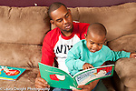 Two year old toddler boy sitting with father read to, boy pointing at picture in book