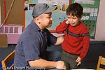 Preschool 3-4 year old male volunteer teacher in training soothing sad and crying boy horizontal