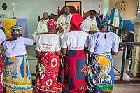 Nigeria. Abakaliki State. Uburu Amach. St. Patrick's Catholic Church. Igbo women kneel in front of catholic priests during a mass celebration for the 25th Priesthood Anniversary of Reverend Father Edward Inyanwachi (the priest seated in the center chair). 14.07.19 © 2019 Didier Ruef