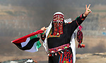 A Palestinian woman waves the national flag during clashes with Israeli security forces in tents protest where Palestinians demanding the right to return to their homeland, at the Israel-Gaza border, in Khan Younis in the southern Gaza Strip, on May 11, 2018. Photo by Yasser Qudih